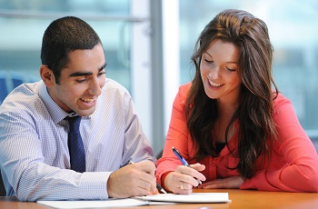 A male and female co-op student reviewing a document